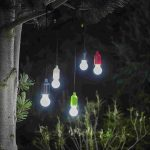 Lys og lygter med logo - helper lamper hænger fra et træ