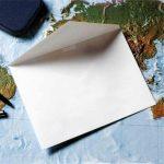Tom, åben konvolut ligger på verdenskort. Konvolutter