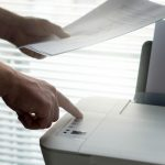 hænder henter brevpapir i printer